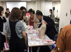 「第8回乳房再建全国キャラバン福岡」ブース展示の商品説明を真剣に聞く参加者